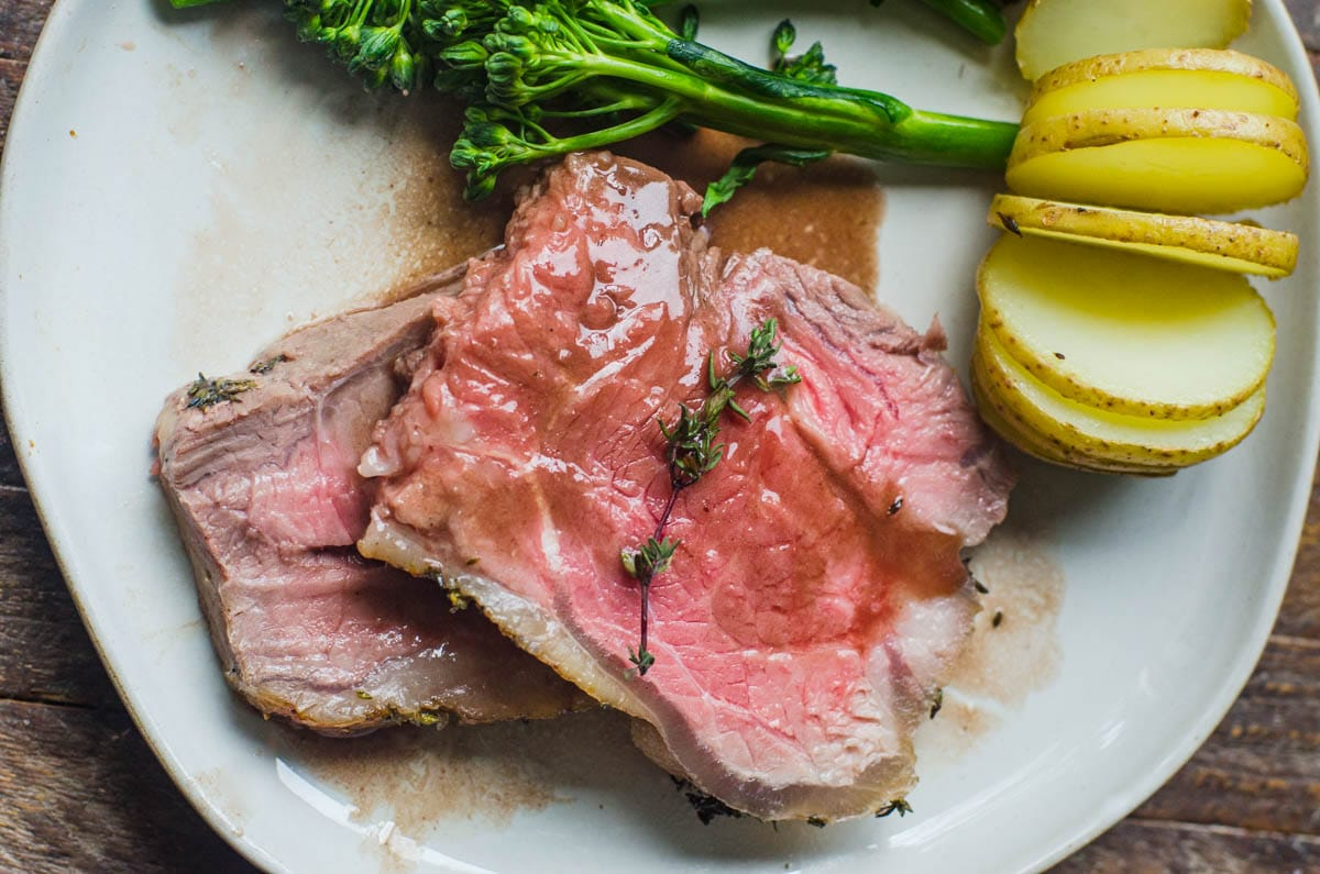 Two slices of New York striploin roast on a plate with potatoes and vegetables