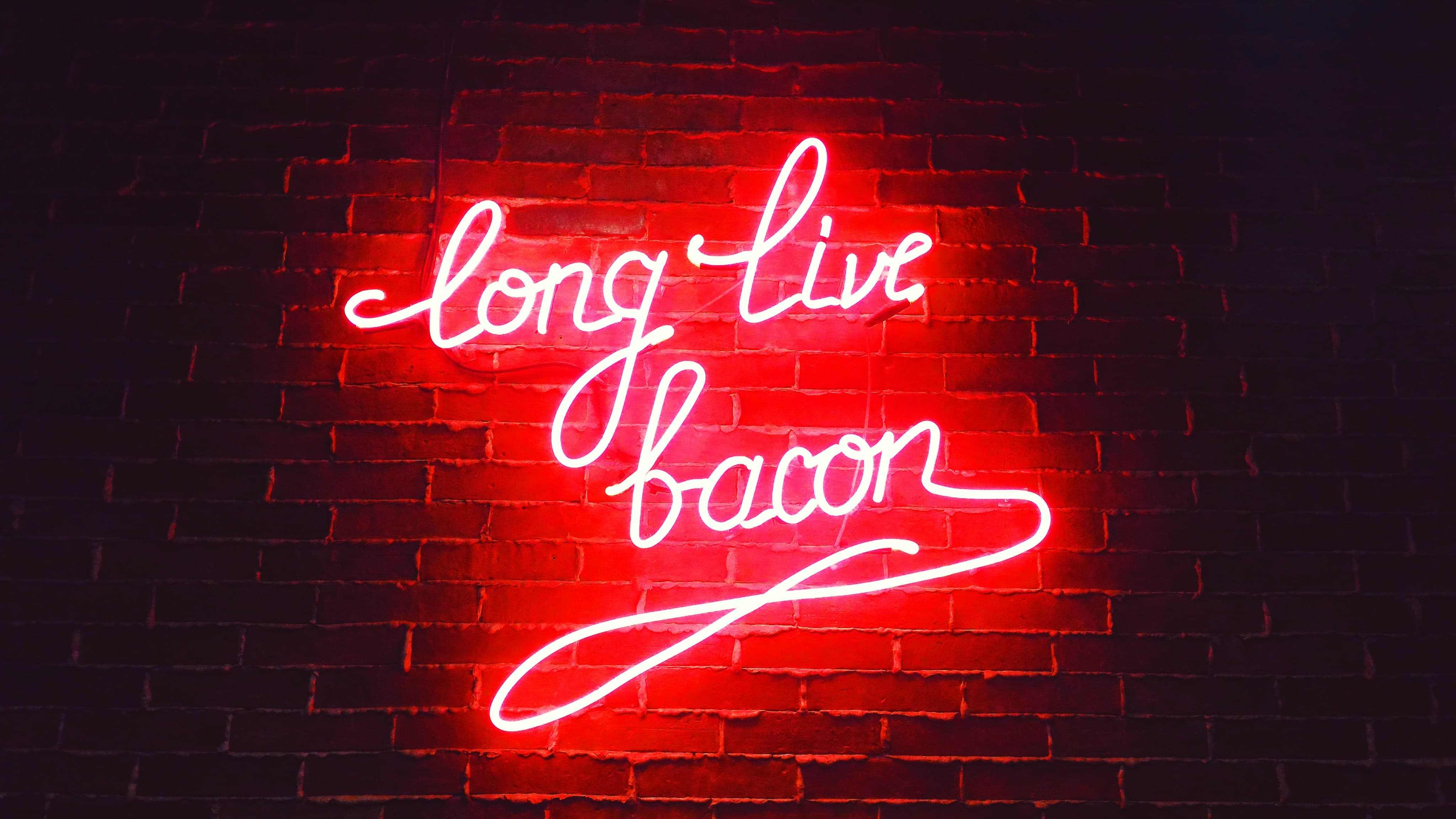 """A neon sign on brick way saying """"long live bacon"""" in red cursive."""