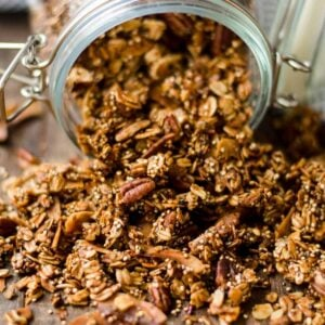 Homemade granola with nuts spilling out of a clear storage jar.