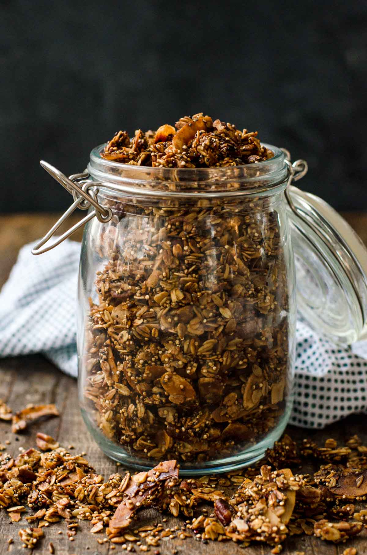 A clear jar of high protein granola on a counter.