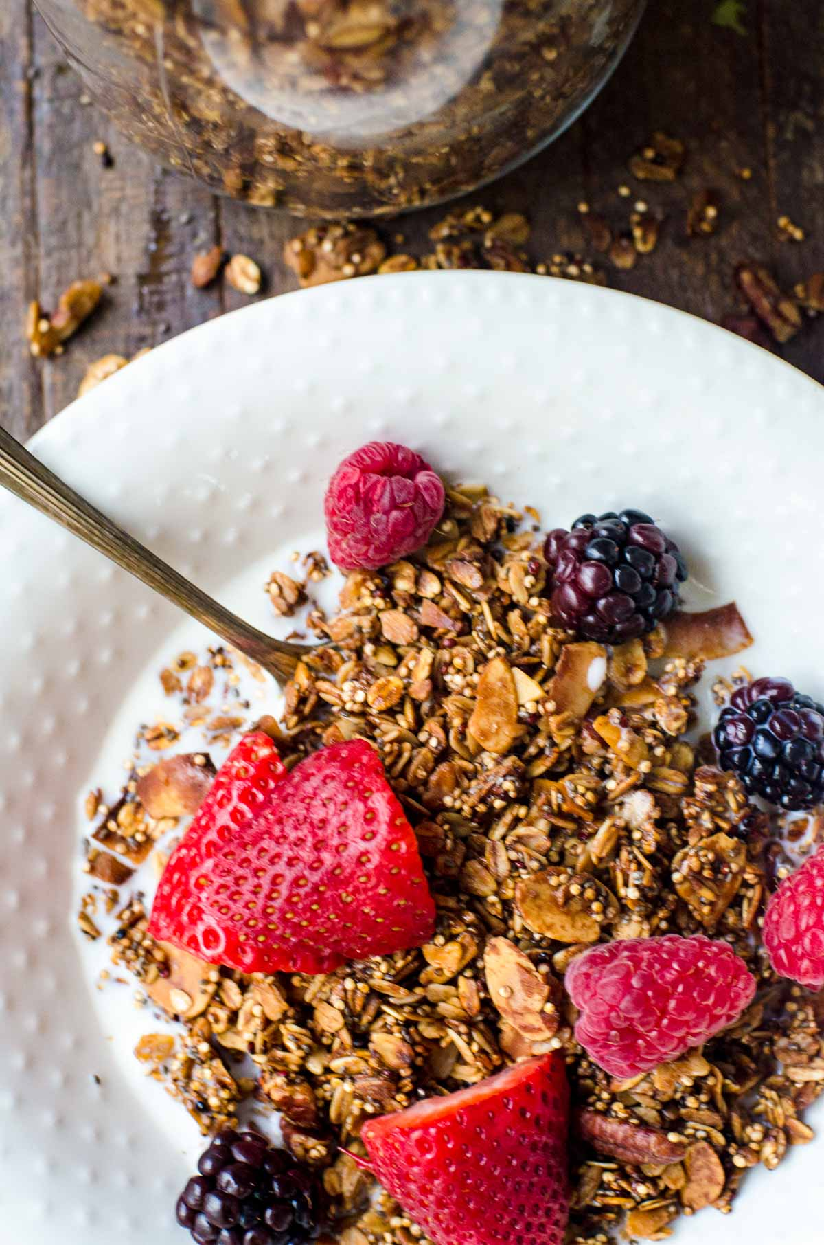 Granola and fresh berries in a white bowl with milk.