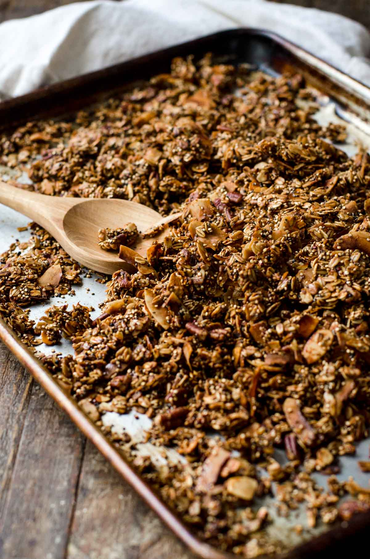 A wooden spoon scraping homemade granola into clusters.