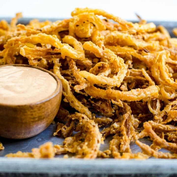 A wooden bowl of sauce next to fried onion strings.
