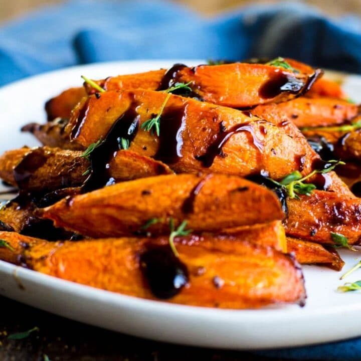 A plate of roasted carrots with balsamic glaze on them.