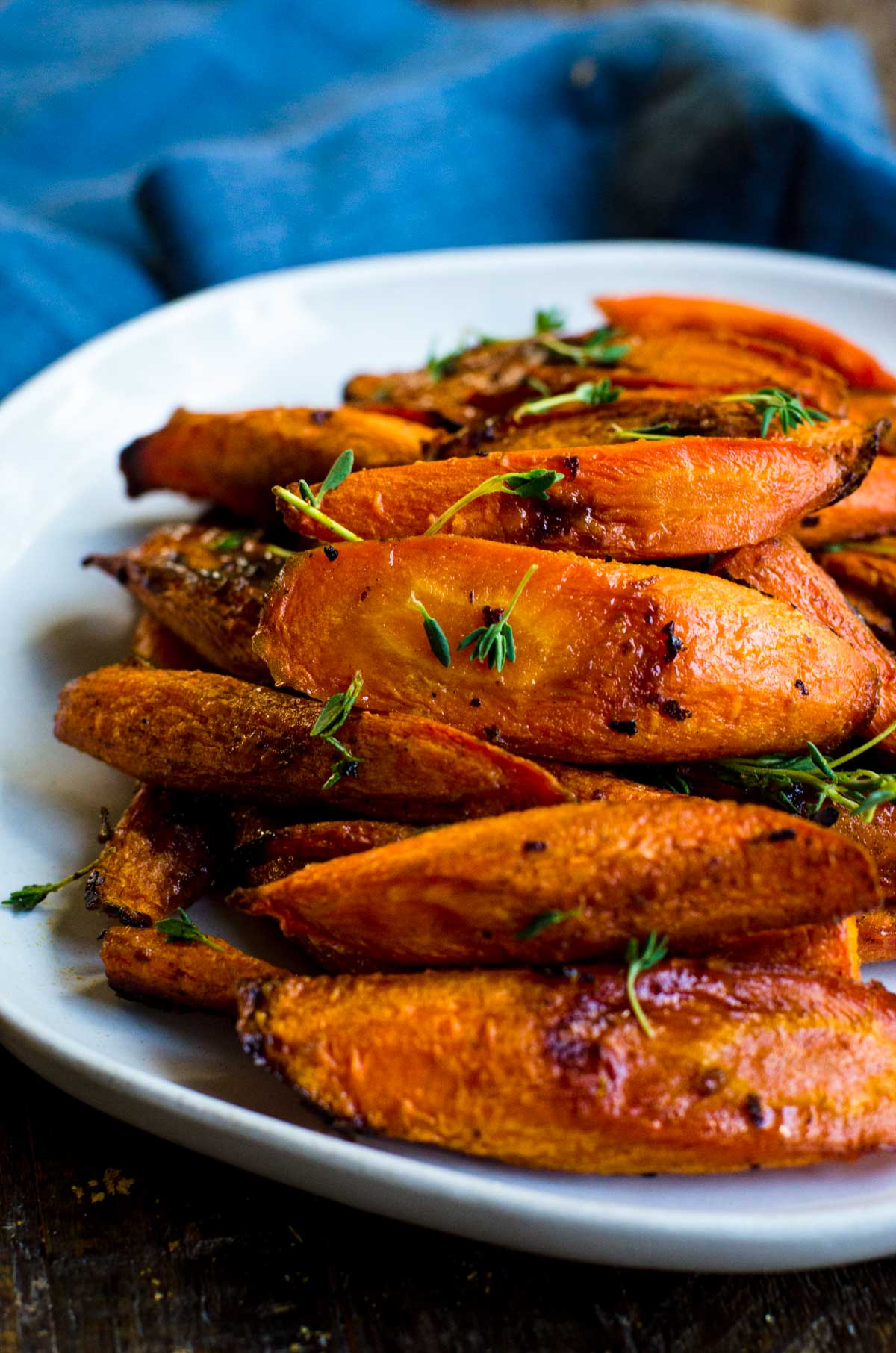 A plate of roasted carrots with fresh thyme.