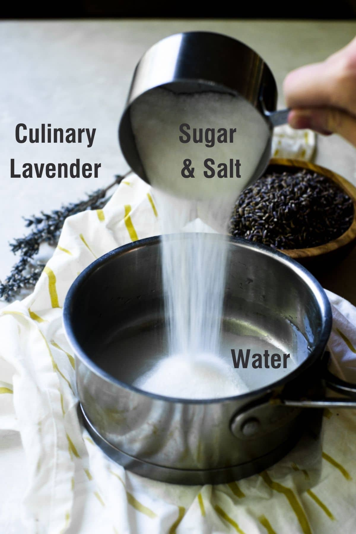 A hand pouring sugar into a pot.  Ingredient names for lavender simple syrup are on it.