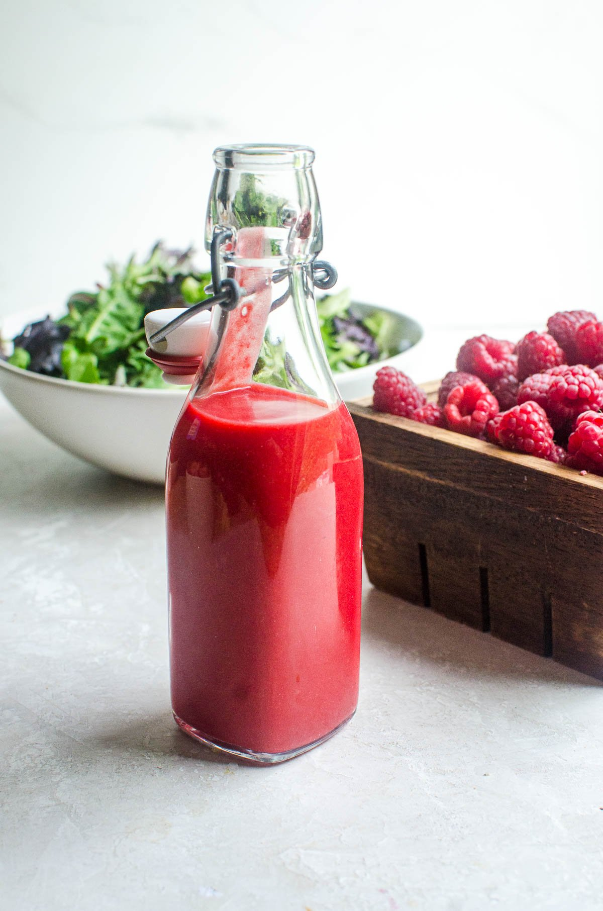 A bottle of raspberry vinaigrette dressing in front of a box of raspberries and bowl of salad.
