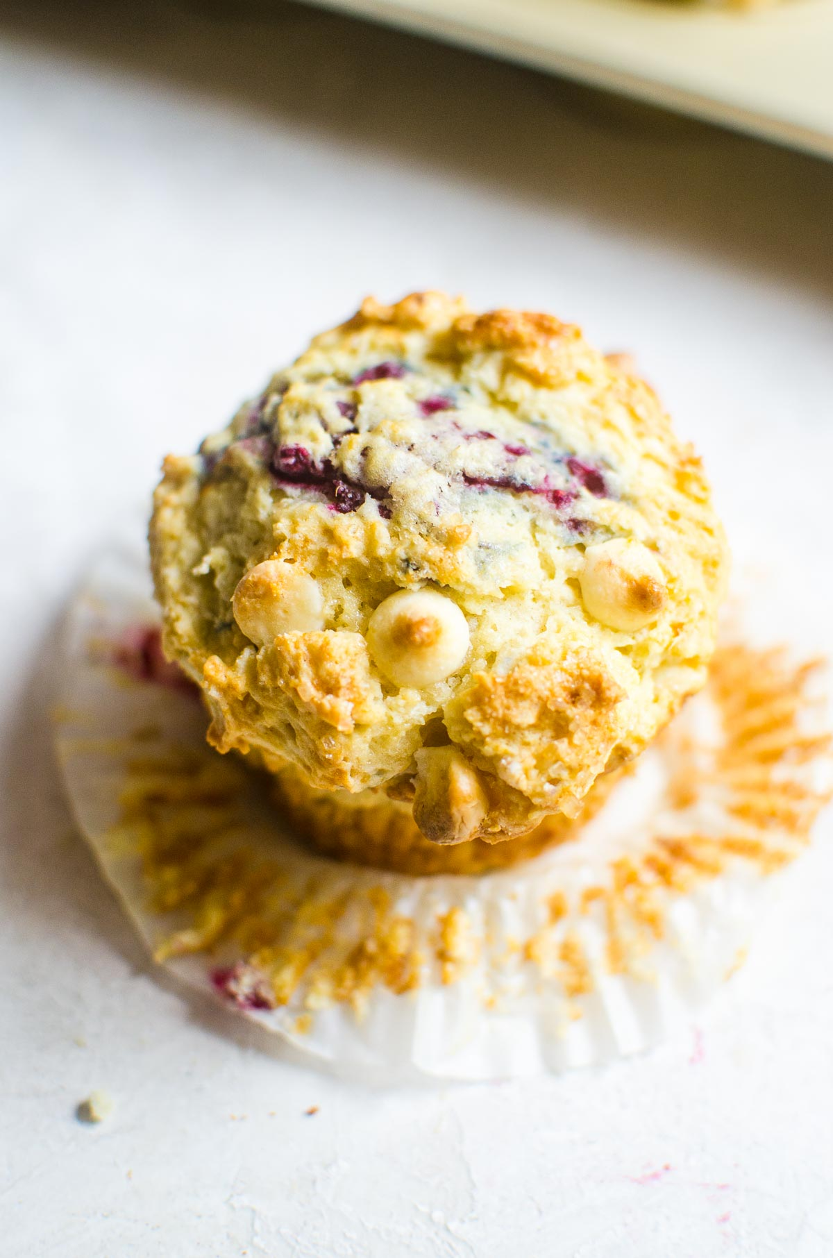 Overhead view of raspberry muffin showing toasted white chocolate.